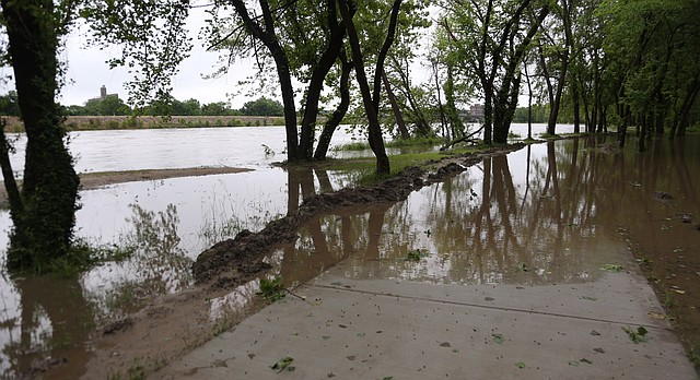 The Kansas River rises over its banks to cover a walking path between Burcham and Constant Parks, Friday morning, May 27, 2016.