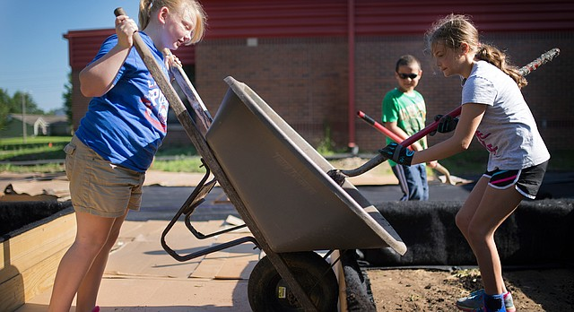 Lawrence girl scout Sally Hubbard lifts a wheelbarrow as Darby Van Fleet shovels out a load of mulch as part of the USD 497 Farm to School program's efforts to construct a raised-bed garden behind Prairie Park School on Friday, July 17, 2015.