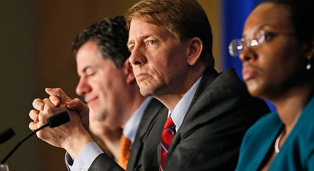 "In this Thursday, March 26, 2015, file photo, Consumer Financial Protection Bureau Director Richard Cordray, center, listens to comments during a panel discussion in Richmond, Va. The CFPB announced Thursday, June 2, 2016, they are proposing a significant clampdown on payday lenders and other providers of high-interest loans, saying borrowers need to be protected from practices that wind up turning into ""debt traps"" for many. ""Too many borrowers seeking a short-term cash fix are saddled with loans they cannot afford and sink into long-term debt,"" Cordray said in a prepared statement. (AP Photo/Steve Helber, File)"