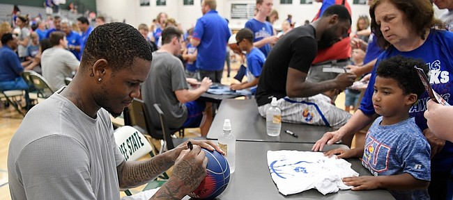 Former Kansas Jayhawk and current Sacramento King Ben McLemore signs a ball after the Rock Chalk Roundball Classic on Thursday at Free State High.