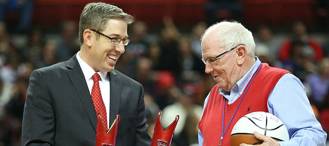 Kansas broadcaster Bob Davis is presented with a pair of Texas Tech cowboy boots by Texas Tech broadcaster Brian Hanni prior to tipoff, Saturday, Jan. 9, 2016 at United Spirit Arena in Lubbock, Texas.