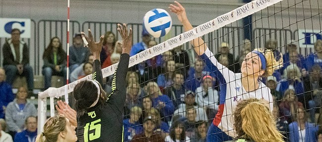 Kansas junior Tayler Soucie spikes the ball past Baylor's Katie Staiger, left, Tola Itiola (15) and Shelly Fanning (5) during their volleyball match Saturday afternoon at the Horejsi Center.