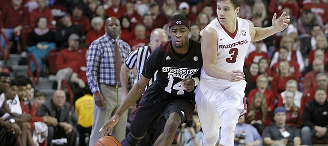 Arkansas' Dusty Hannahs (3) keeps close to Mississippi State's Malik Newman (14) during the second half of an NCAA college basketball game Saturday, Jan. 9, 2016, in Fayetteville, Ark. Arkansas beat Mississippi State 82-68. (AP Photo/Samantha Baker)