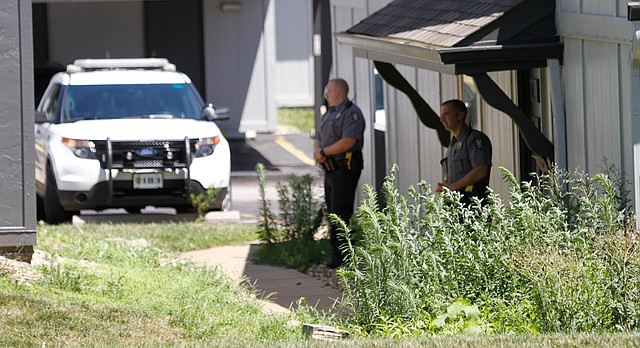 Law enforcement officers stand guard at an apartment complex in the 2500 block of West Sixth Street, where police say an infant was found in a trash receptacle early Thursday, July 7, 2016.
