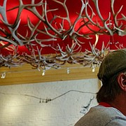 The interesting cafe ceiling display of antlers caught my eye first. But rather than photograph just the ceiling, I put my camera at a low angle to include my cycling friend Tom Mersmann in the foreground. The photo now has a greater sense of depth and a viewers eye moves between two visually interesting subjects.
