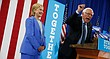 Democratic presidential candidate Hillary Clinton listens as Sen. Bernie Sanders, I-Vt., speaks during a rally in Portsmouth, N.H., Tuesday, July 12, 2016, where Sanders endorsed Clinton. (AP Photo/Andrew Harnik)