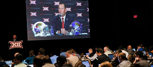 Members of the media work as Kansas head football coach David Beaty, seen on large vide screen, responds to questions during Big 12 media days, Monday in Dallas.