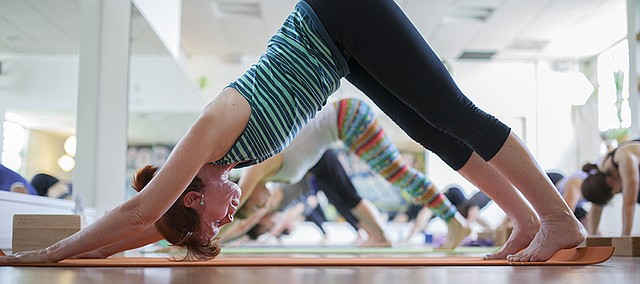 Hot Hatha yoga student Janet Buie, of Lawrence, goes into the down dog pose along with the rest of the class on Friday, July 22, 2016 at OmTree Shala, 1405 Massachusetts St.
