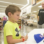 Former Kansas University star forward Perry Ellis signs an autograph for five-year-old Packson McDaniel, of Lawrence, Saturday afternoon at Hy-Vee, 3504 Clinton Parkway.