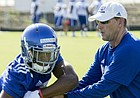 Kansas coach David Beaty hands the ball off to junior running back James Sullivan as they run through drills during practice on Thursday, Aug. 4, 2016.