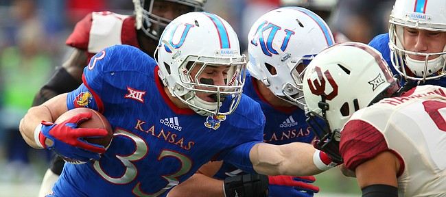 Kansas kick returner Ryan Schadler (33) collides with the Oklahoma defense on a kickoff return during the second quarter Saturday, Oct. 31, 2015 at Memorial Stadium.
