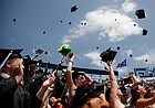 Graduates toss their caps after the conferral of degrees during the 2011 commencement at Memorial Stadium on Sunday, May 22, 2011.