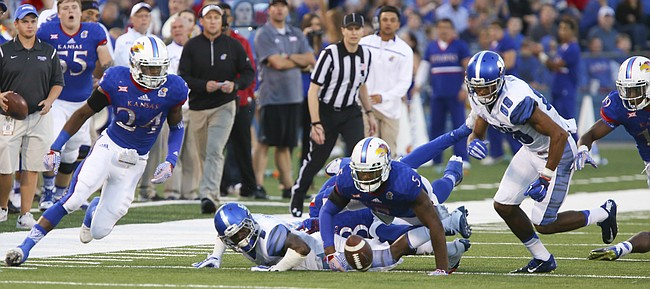 Kansas safety Bazie Bates IV (24) and linebacker Marcquis Roberts eye a fumbled ball during the second quarter on Saturday, Sept. 12, 2015 at Memorial Stadium.