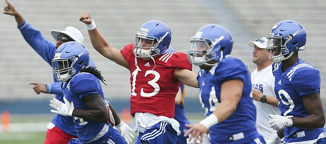 Kansas quarterback Ryan Willis, (13) and other Jayhawk players rush to the field in excitement after a catch in the end zone on a game-winning play scenario, during practice on Monday, Aug. 15, 2016 at Memorial Stadium.