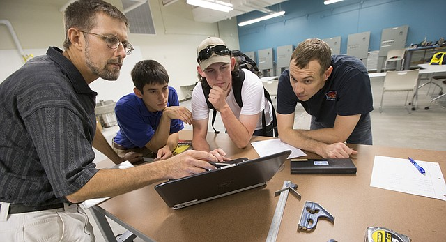 Instructor John Rasmussen, left, leads his students Matt Day, John Bradshaw and Matt Brummer through some course information on Wednesday, Aug. 10, 2016 during a Flint Hills Technical College industrial mechanics class at the Dwayne Peaslee Technical Training Center, 2920 Haskell Ave. The center is beginning its second year and is seeking supplemental funding from Douglas County.
