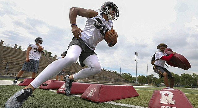 Lawrence High running back Trey Moore makes a cut around a pad as he runs drills with the running backs during the first day of practice on Monday, Aug. 15, 2016 at Lawrence High School.