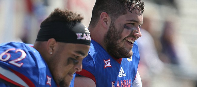 Kansas offensive lineman Joe Gibson (77) has a laugh next to fellow position player D'Andre Banks (62) on the bench during the Spring Game on Saturday, April 9, 2016 at Memorial Stadium.