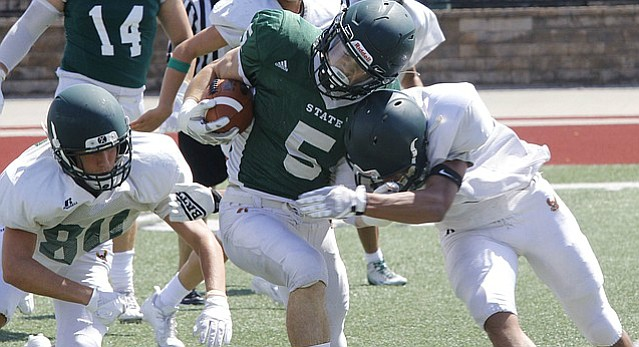 Free State junior running back Gage Foster absorbs a hit during the football team's preseason scrimmage on Saturday, August 20.