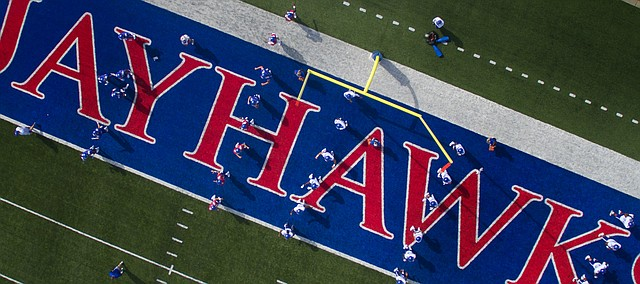 The Kansas Jayhawks, coaches and staff position themselves around the field and in the end zone for stretches during practice on Friday, Aug. 19, 2016 at Memorial Stadium.