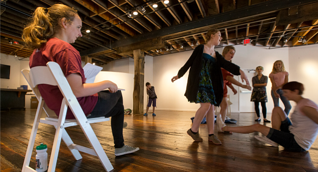 "Director Leah Towle watches a scene in which Zora Lotten Barker, front center, and Jillian Schwartz, who are playing the roles of The Twins, shove Allison Wilson, who is playing the role of Non-Binary, to the ground, during a rehearsal for ""Ladies of the Fly"" on Monday, Aug. 22, 2016 at Cider Gallery, 810 Pennsylvania. The play, which is produced by Orange Mouse Theatricals and is inspired by William Golding's The Lord of the Flies, features an all-female cast of young, local actors."