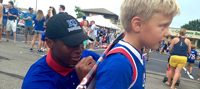 Kansas sophomore defensive end Dorance Armstrong Jr. crouches low to the ground to sign a young fan's poster on Aug. 26, 2016, at the KU Kickoff at Corinth Square, in Prairie Village.