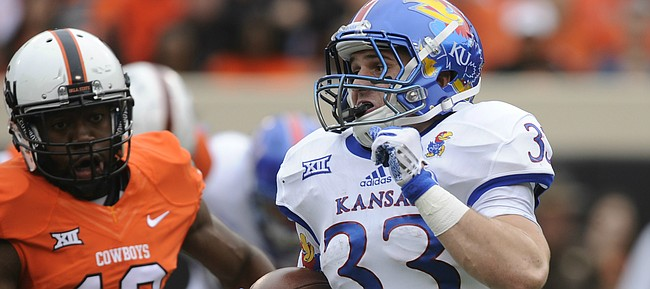 Kansas wide kick returner Ryan Schadler (33) looks for a hole as he is tailed by Oklahoma State special teams player Kirk Tucker (12) during the second quarter on Saturday, Oct. 24, 2015 at T. Boone Pickens Stadium in Stillwater, Okla.