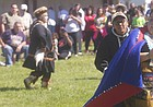 Haskell University junior Grace Denning dances and beats a drum as freshman Andy Piscoya looks during a dance they and other members of the school's Alaskan Club performed Saturday, Sept. 10, at the 28th annual Haskell Indian Art Market. The club will perform again at noon Sunday as the art market returns from 10 a.m. to 5 p.m. to Haskell.