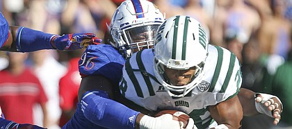 Kansas defensive tackle Daniel Wise (96) wraps up Ohio running back Dorian Brown (28) during the fourth quarter on Saturday, Sept. 10, 2016 at Memorial Stadium. At left is Kansas defensive end Dorance Armstrong Jr. (2).