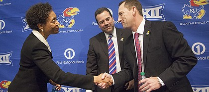 Kansas University chancellor Bernadette Gray-Little, left, shakes hands with new head football coach David Beaty, right, after an introductory press conference Monday, Dec. 8, 2014, at the Anderson Family Football Complex at KU in Lawrence, Kan. Beaty, the wide receivers coach and recruiting coordinator at Texas A&M, was hired by KU Friday. At center is Sheahon Zenger, KU director of athletics.