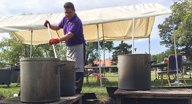 Haskell Indian Nations University cafeteria worker Benjamin Rowland cooks pots of bison chili, bison hominy stew and sweet corn bison stew over an open flame on the Haskell campus Thursday, Sept. 22, 2016. The food was for a bison feast planned in conjunction with a two-day conference on climate change being held at the university.