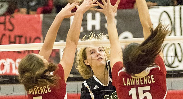 Free State High sophomore Rachel Hickman (28) overpowers Lawrence High blockers Katelyn Mask (7) and Abby Percich (15) at the net during their match Tuesday at LHS.