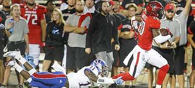 Kansas linebacker Mike Lee (11) can't hang on as Texas Tech receiver Keke Coutee (20) slips away on a touchdown run during the third quarter on Thursday, Sept. 29, 2016 at Jones AT&T Stadium in Lubbock, Texas.