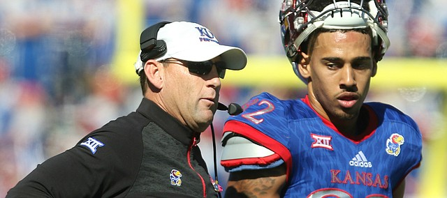 Kansas head coach David Beaty talks with wide receiver Shakiem Barbel (82) late in the fourth quarter on Saturday, Oct. 8, 2016 at Memorial Stadium.