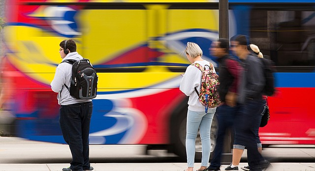 A bus whirs by as University of Kansas students wait along Jayhawk Boulevard on Wednesday, Oct. 12, 2016.