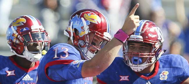 Kansas quarterback Ryan Willis (13) celebrates a touchdown with teammates Steven Sims Jr. (11) and D'Andre Banks (62) during the third quarter on Saturday, Oct. 8, 2016 at Memorial Stadium.