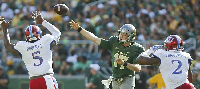 Baylor quarterback Seth Russell (17) throws between Kansas linebacker Marcquis Roberts (5) and defensive end Dorance Armstrong Jr. (2) during the second quarter on Saturday, Oct. 15, 2016 at McLane Stadium in Waco, Texas.