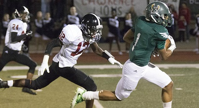 Free State High  senior Zack Sanders (1) sprints past Lawrence High junior Ekow Boye-Doe (12) and into the end zone for a touchdown during their game Friday night at FSHS.