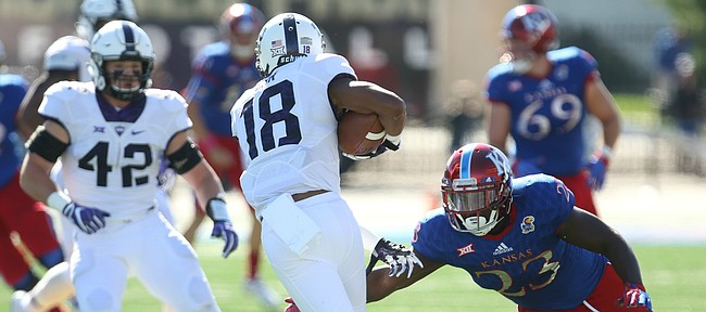Kansas running back Denzell Evans (23) misses a tackle on TCU safety Nick Orr (18) after Orr's interception during the first quarter on Saturday, Oct. 8, 2016 at Memorial Stadium.