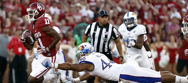 Oklahoma wide receiver Dede Westbrook (11) runs for a touchdown as Kansas defensive end Cameron Rosser (46) misses a tackle during the first half of an NCAA college football game in Norman, Okla., Saturday, Oct.29, 2016.