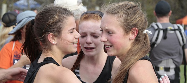 Free State sophomores Julia Larkin, left, and Emma Hertig, center, hug senior Emily Venters after finding out they won the Class 6A girls cross country state title Saturday at Rim Rock Farm. Venters was the state runner-up with a time of 18:09.9, and Larkin and Hertig came in 16th and 28th, respectively, to help the Firebirds win their first state championship since 2013.