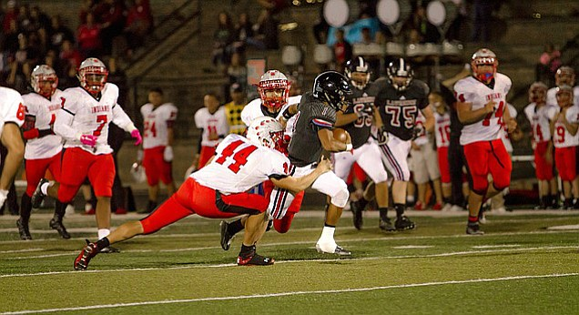 Lawrence High quarterback Dante Jackson (#1) breaks a tackle for a long run against Shawnee Mission North on Friday in the Class 6A state playoffs.