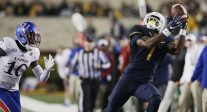 West Virginia wide receiver Shelton Gibson (1) makes a catch as Kansas cornerback Marnez Ogletree (10) closes in for the tackle during the first half of an NCAA college football game, Saturday, Nov. 5, 2016, in Morgantown, W.Va.