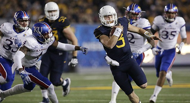 West Virginia quarterback Skyler Howard (3) slips by Kansas safety Shaquille Richmond (4) on his way to a touchdown during the first half of an NCAA college football game, Saturday, Nov. 5, 2016, in Morgantown, W.Va.