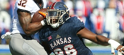 Kansas defensive tackle Daniel Wise (96) looks to bring down Oklahoma State running back Chris Carson (32) during the second quarter on Saturday, Oct. 22, 2016 at Memorial Stadium.