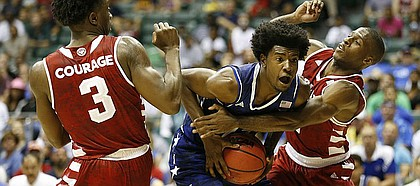 Kansas guard Josh Jackson (11) is smothered under the net by Indiana guard Josh Newkirk (2) and Indiana forward OG Anunoby (3) during the second half of the Armed Forces Classic at Stan Sheriff Center, on Friday, Nov. 11, 2016 in Honolulu, Hawaii.