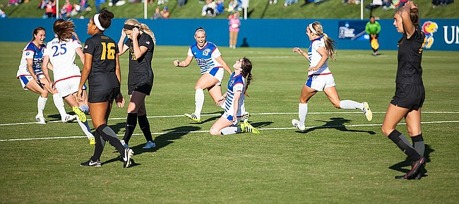 Kansas junior forward Lois Heuchan slides to the turf after scoring the game-winning goal against Missouri in the first round of the NCAA Tournament on Sunday, Nov. 13, 2016 at Rock Chalk Park. Senior Hanna Kallmaier (23) pumps her fist in the background.