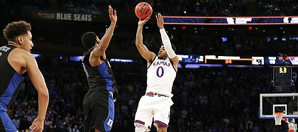 Kansas guard Frank Mason III (0) puts up the final shot over Duke guard Matt Jones (13) with seconds remaining for the win on Tuesday, Nov. 15, 2016 at Madison Square Garden in New York.