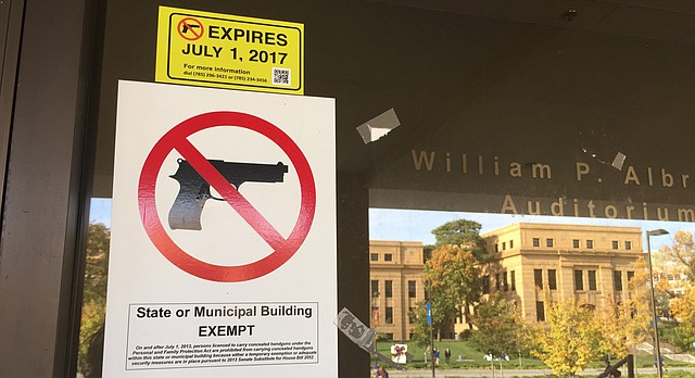 No guns allowed signs are posted on doors leading into Wescoe Hall on the University of Kansas campus on Monday, Oct. 17, 2016. Jayhawk Boulevard and Strong Hall are reflected in the glass.