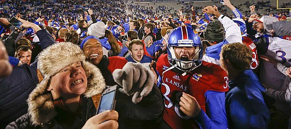 Kansas fans and players go crazy on the field following the Jayhawks' 24-21 overtime upset of Texas on Saturday, Nov. 19, 2016 at Memorial Stadium.
