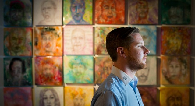 Lawrence artist John Sebelius is pictured before a wall of portraits from his upcoming show, Cupcakes, which opens on Black Friday at Phoenix Gallery. The show features 65 portraits of various encounters with people Sebelius has met through his travels around the country.